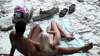 Beach voyeur finds a petite blonde enjoying a black cock