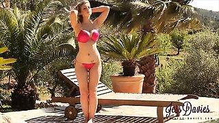 Jess Davies strips from red bikini by the pool.