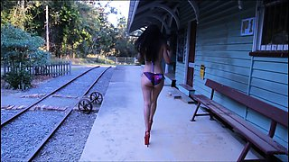 Sexy slender brunette in high heels flaunts her body outside